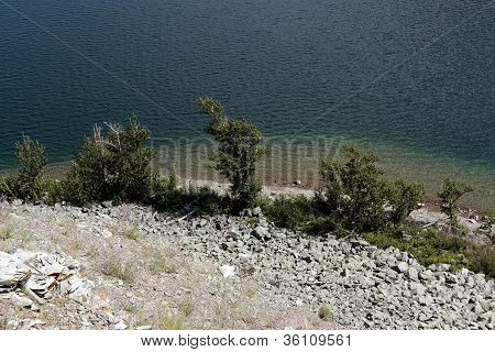Rocky slope, shrubs, and water