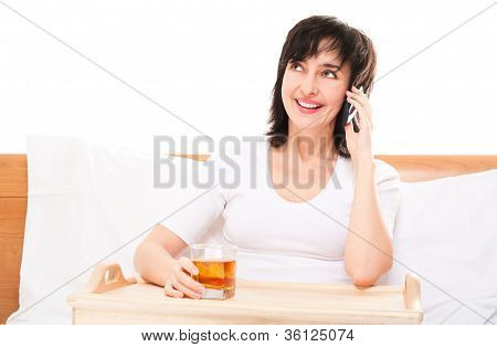 Woman In Bed Talkin By Phone With Glass On Juice On Tray