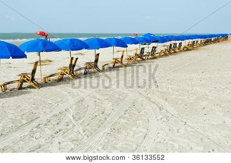 Beach lounge chairs with umbrellas