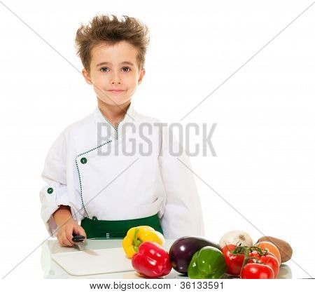 Little Boy Chef In Uniform With Knife Cutting Vegetables