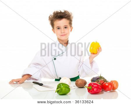 Little Boy Chef In Uniform With Knife Cooking Vegatables Holding Yellow Paprika