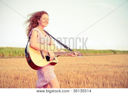Redhead Woman Playing Guitar Outdoors