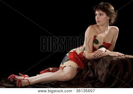 Beautiful Sexy Young Woman In Strapless Long Dress Gracefully Reclines On Dark Velvet Fabric