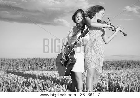 Two Young Women Playing Guitar And Violin Outdoors. Grayscale.