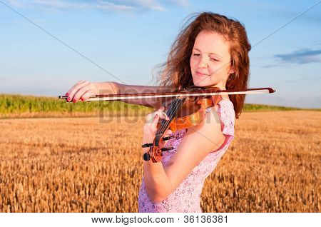 Redhead Woman Playing Violin Outdoors On The Field