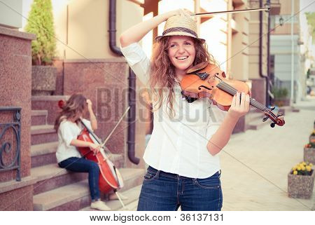 Women Strings Duet Playing Violin And Cello On The Street