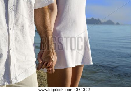 Couple On The Beach Holding Hands
