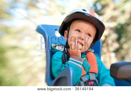 Little Boy In Bike Child Seat Eating Cracker