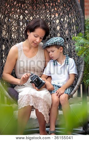 Mother and little son with retro camera outdoors