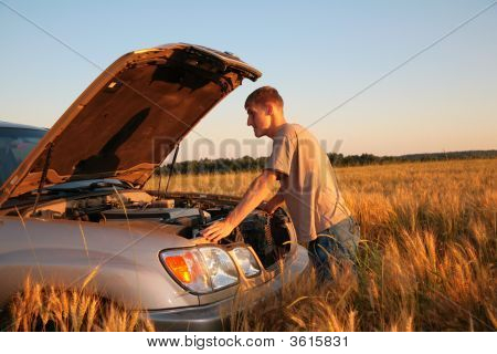 Man At Offroad Car With Lifted Cowl On Wheaten Field