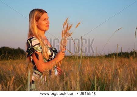 Young Woman With Earns On Weaten Field