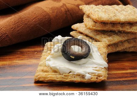 Cracker With Cream Cheese And An Olive