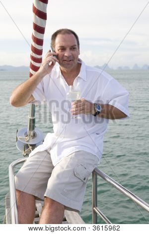 Man On Yacht With Mobile Phone And Wine