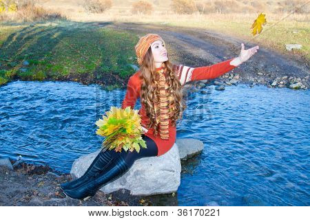 Beautiful Girl With Long Curly Hair Into Knitted Garments Cast A Maple Leaf In The River Fall