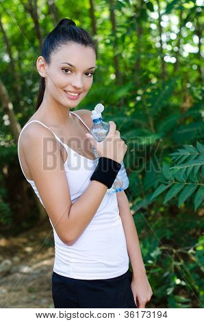 Beautiful girl smiling holding a bottle of water outdoors