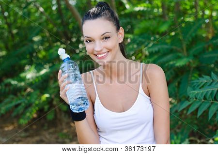 Beautiful girl laughing holding a bottle of water outdoors