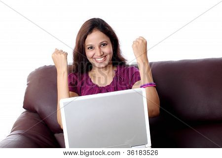 Excited Woman With Laptop On Sofa