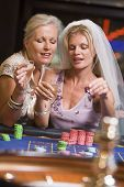 picture of hen party  - Woman in bridal veil with another woman in casino playing roulette and smiling  - JPG