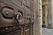 Old wooden door, knockers and stone made door-post