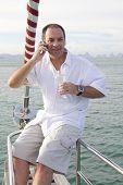 Постер, плакат: Человек на яхте с мобильного телефона и вино