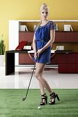 stock photo of ladies golf  - beautiful blonde girl in full lenght plays golf with blue short dress and hig shoes takes golf - JPG