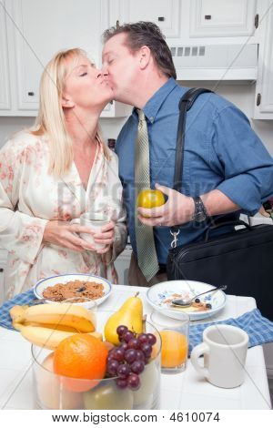 Businessman Kisses His Wife In Kitchen