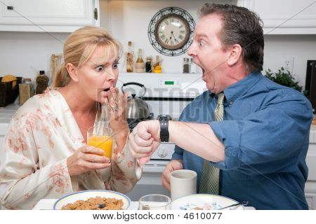 Surprised Couple In Kitchen Late For Work