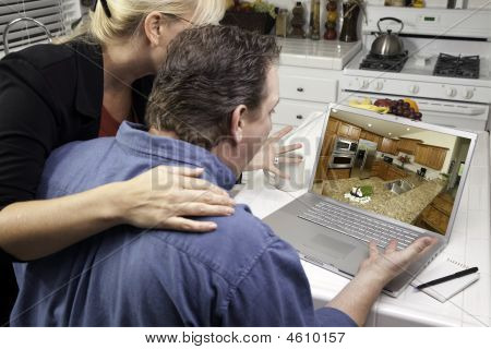 Couple In Kitchen Using Laptop - Home Improvement