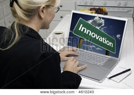 Woman In Kitchen Using Laptop