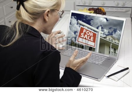 Excited Woman In Kitchen Using Laptop  - Real Estate Shopping