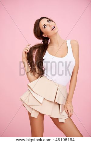 Cute brunette posing before pink background and looking up