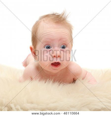 Funny baby lying on a sheep fur.