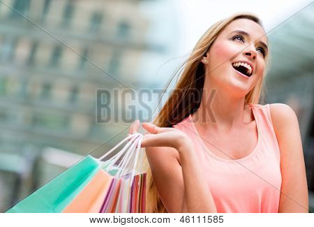 Shopping girl looking up daydreaming and holding bags