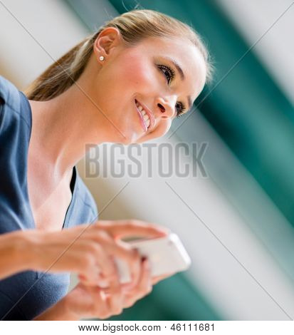 Business woman holding cell phone and texting