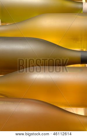Closeup of a wooden crate of chardonnay wine bottles. Vertical format with shallow depth of field, focus is on second bottle.