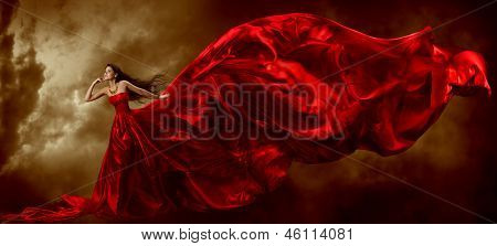 Woman In Red Waving Beautiful Dress With Flying Fabric Over Artistic Sky Background