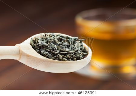 Green Tea Leaves In Wooden Spoon, Cup Of Tea On Background