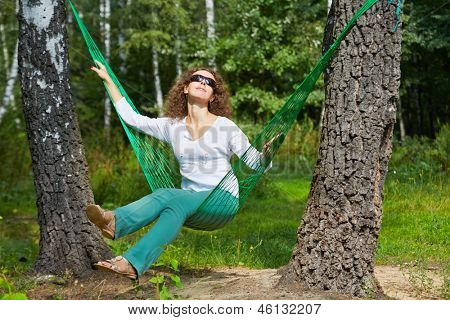 Young smiling woman in dark sunglasses sits in hammock, turning his face to the sun