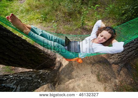 Young barefooted woman lies in hammock, notebook lies on her stomach, high angle view