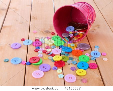 Colorful buttons strewn from bucket on wooden background