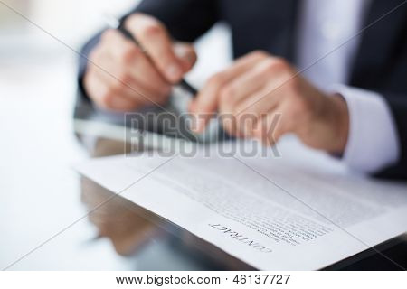Close-up of male hands with pen over business document