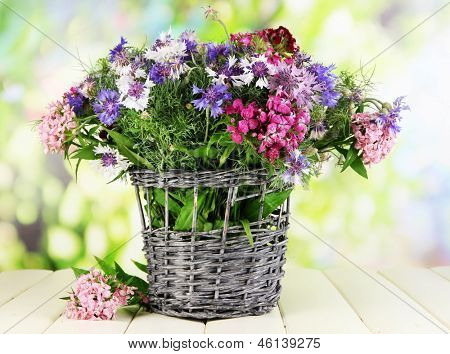 Beautiful bouquet in basket on wooden table on natural background