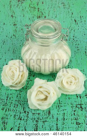 Sugar roses, glass jar with sugar,  on color background