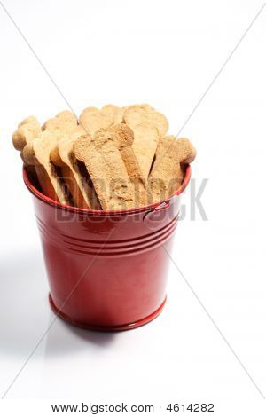 Closeup Of Brown Dog Treats In A Red Bucket.