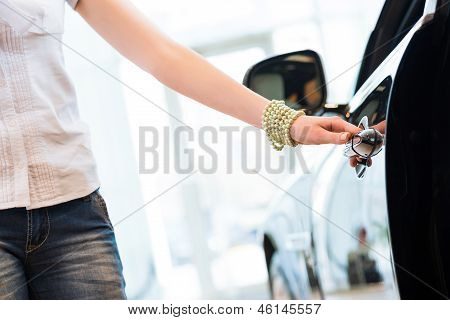 woman opens the door to a new car