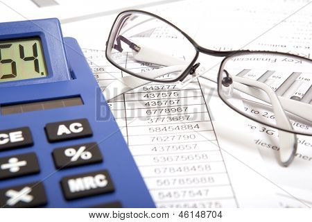 Glasses and calculator on paper table with finance report