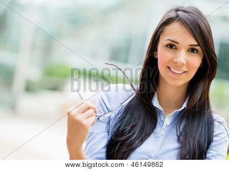Mulher de negócios casuais segurando óculos e sorrindo