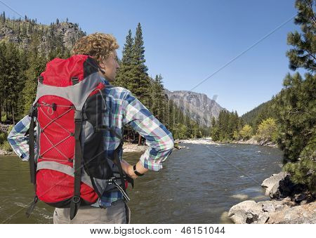 Hiker, with backpack, standing on the banks of the Wenatchee River, near Leavenworth in the Cascade Mountain range, Washington State, USA