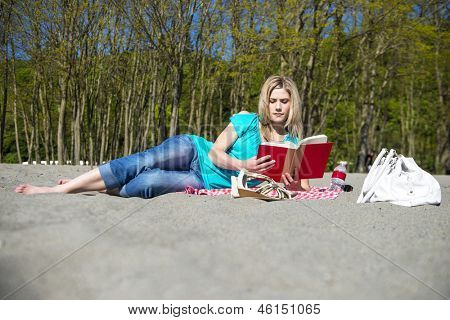 Young Woman Lying on her side in the Sand Reading Book At Beach