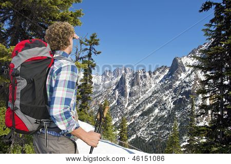 Hiker admiring the view on the snowy mountains of the Kangaroo ridge from the Washington Pass overlook in the North Cascades Range, with the melting snow on a warm spring day